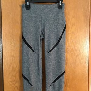 Grey capris with black mesh inserts.